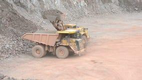 Aardeverhuizer die een kipwagenvrachtwagen met stenen in een steengroeve, oppervlaktemijn laden typische mijnbouw stock videobeelden
