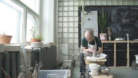 In aardewerkworkshop snijdt de vakman vorm van een kleikom met een hulpmiddel stock footage