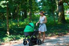 Aardgang met wandelwagen, jonge moeder die in mooie kleding op de bosgang met haar baby in de kinderwagen lopen royalty-vrije stock foto's