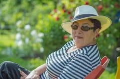 aardige bejaarde dame die in een hoed en zonnebril op een stoel in de tuin zitten Stock Afbeelding