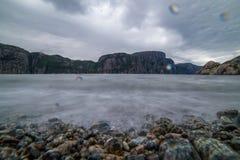 Aardlandschap met een mening van bergen op de kust van een fjor Stock Foto