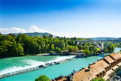 Aare river in Bern. With dam and bridge behind the red houses roofs stock photos