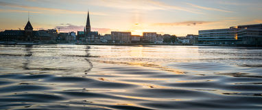 Aarhus sunset, Denmark. The huge tower of the cathedral of Aarhus dominates the skyline - sunset over the harbour waters with small and smooth waves Royalty Free Stock Images