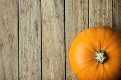 Abóbora alaranjada brilhante grande no espaço de madeira da cópia do fundo da prancha para o texto outono da colheita da ação de  Fotografia de Stock Royalty Free