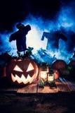 Abóbora alaranjada de Dia das Bruxas com os espantalhos no campo Fotografia de Stock