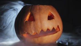 Abóbora cinzelada de Dia das Bruxas, em torno do fumo em um close-up preto do fundo filme