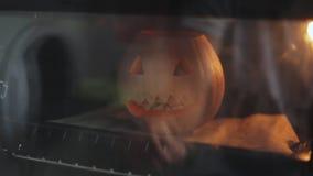 A abóbora cinzelada no partido de Dia das Bruxas é cozida no forno enchido com maçãs Close-up filme