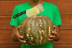 Abóbora da terra arrendada do cozinheiro chefe do homem e faca do talhador Fotos de Stock Royalty Free