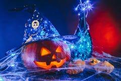 Abóbora de Dia das Bruxas com chapéu em uma Web de aranha com doces e iluminação escura Conceito da doçura ou travessura em azul  Foto de Stock Royalty Free