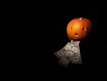 Abóbora de Dia das Bruxas com dólar no fundo preto Imagem de Stock