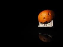 Abóbora de Dia das Bruxas com dólar no fundo preto Fotos de Stock Royalty Free