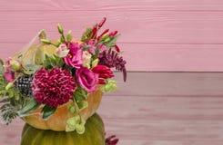 Abóbora de Dia das Bruxas com flores e folhas na tabela do espelho foto de stock