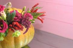 Abóbora de Dia das Bruxas com flores e folhas na tabela do espelho fotografia de stock royalty free
