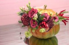 Abóbora de Dia das Bruxas com flores e folhas na tabela do mirrow foto de stock royalty free
