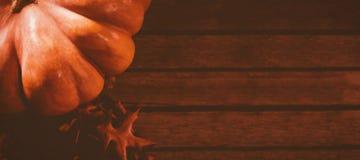Abóbora pelas folhas de outono na tabela de madeira Fotografia de Stock