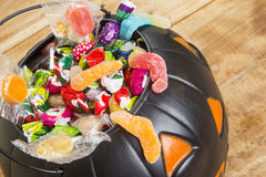 A abóbora plástica preta encheu-se com os doces na tabela de madeira Fotos de Stock Royalty Free