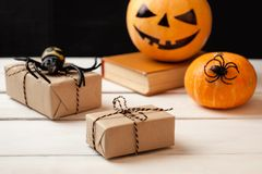 Abóbora três com caras pintadas, caixas de presente e as aranhas decorativas em uma tabela de madeira em um fundo de placas preta Fotos de Stock Royalty Free