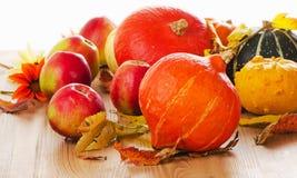 Abóboras alaranjadas com maçãs e folhas da queda isoladas em b branco Imagens de Stock Royalty Free