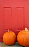 Abóboras alaranjadas e porta vermelha Foto de Stock Royalty Free