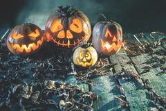 Abóboras de Dia das Bruxas no fundo de madeira Caras assustadores cinzeladas da abóbora Fotografia de Stock