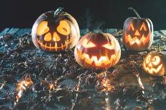 Abóboras de Dia das Bruxas no fundo de madeira Caras assustadores cinzeladas da abóbora Fotografia de Stock Royalty Free