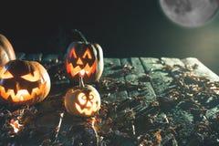 Abóboras de Dia das Bruxas no fundo de madeira Caras assustadores cinzeladas da abóbora Imagens de Stock