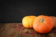 Abóboras e folhas de outono no fundo de madeira ação de graças e conceito do Dia das Bruxas Fotos de Stock Royalty Free