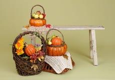 Abóboras e maçãs nas cestas no banco de madeira Imagens de Stock