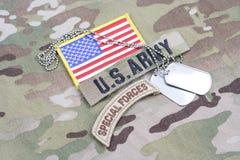 Aba das forças especiais de EXÉRCITO DOS EUA, remendo da bandeira, com a etiqueta de cão no uniforme da camuflagem fotografia de stock