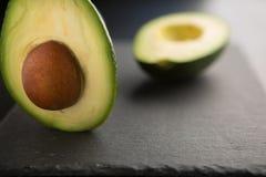 abacate cortado em um fundo escuro fotos de stock