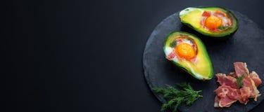 Abacate cozido com um ovo em um espaço preto do fundo e da cópia fotografia de stock
