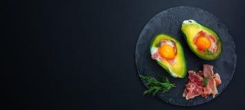 Abacate cozido com um ovo em um espaço preto do fundo e da cópia foto de stock royalty free