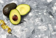 Abacate e medida da fita no fundo cinzento, conceito da dieta imagem de stock royalty free