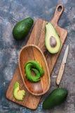 Abacate fresco cortado em uma bacia de madeira em uma placa de corte Vista de acima fotos de stock royalty free