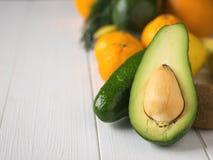 Abacate, tangerinas, laranjas, quivi e bananas cortados na tabela do branco do vintage Alimento do vegetariano Imagens de Stock