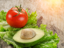 Abacate, tomates e salada na placa de madeira Imagens de Stock Royalty Free