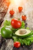 Abacate, tomates e salada na placa de madeira Fotos de Stock Royalty Free