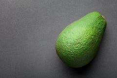 Abacate verde isolado no fundo escuro Imagens de Stock