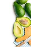 Abacates verdes com faca e placa de corte imagens de stock royalty free