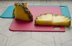 Abacaxi cortado em placas de corte cor-de-rosa e azuis Imagem de Stock Royalty Free