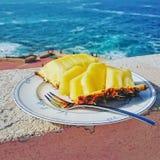 Abacaxi cortado maduro e suculento na placa contra o mar azul imagens de stock