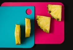 Abacaxi cortado na placa de corte, fundo colorido abstrato Foto de Stock Royalty Free
