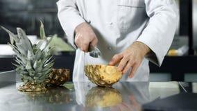Abacaxi do corte do cozinheiro chefe no movimento lento Mãos do cozinheiro chefe do close up que desbastam o fruto fresco filme