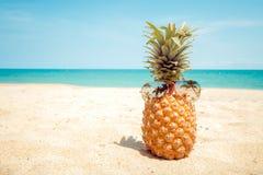 Abacaxi do moderno com óculos de sol em um Sandy Beach fotografia de stock royalty free
