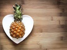 Abacaxi em uma placa coração-dada fôrma Foto de Stock Royalty Free