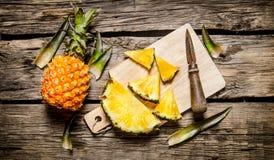 Abacaxi fresco cortado com uma faca em uma placa de desbastamento Fotos de Stock