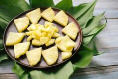 Abacaxi fresco cortado em uma bacia nas folhas Foto de Stock