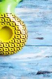 Abacaxi inflável em uma superfície de madeira rústica azul Imagem de Stock