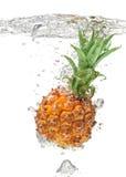 Abacaxi pequeno que cai na água no branco Fotografia de Stock