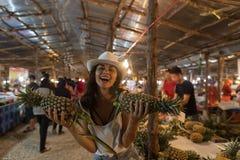 Abacaxis alegres da posse da menina que compram no mercado de rua tropical no turista da jovem mulher de Tailândia que compra fru Imagens de Stock Royalty Free
